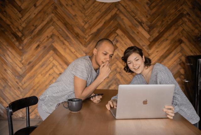 איש ואשה רואים סרטון במחשב וצוחקים
