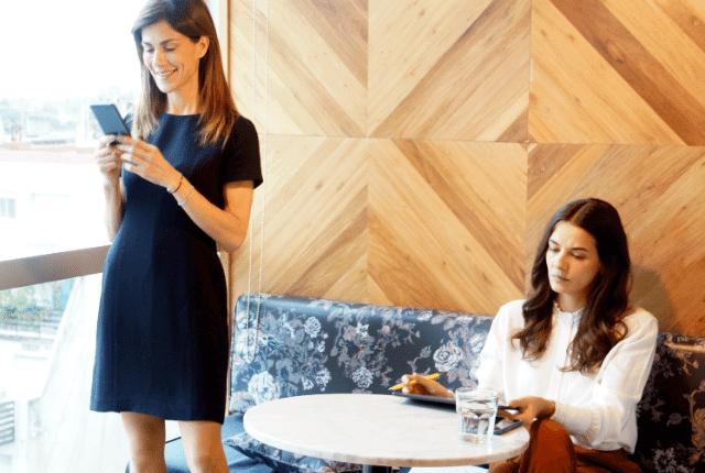 אישה יושבת ואישה עומדת עם פלאפון